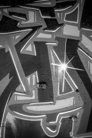 graphiti: spraypaint, a city wall with graffiti in black and white, urban art