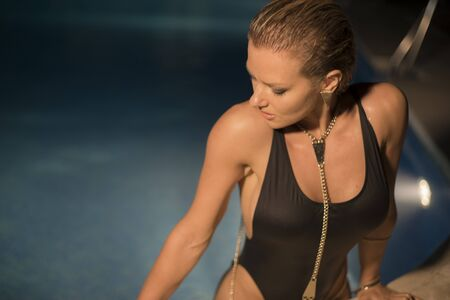 chic woman: chic, beautiful blond woman in a swimsuit in a pool at night