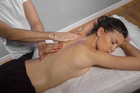 Wellness. Masseur doing massage on woman body in the spa salon. Beauty treatment concept. Stock Photo