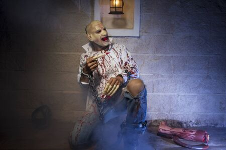 severed: zombie, Man chained with blood and knife, has a severed leg blood Stock Photo