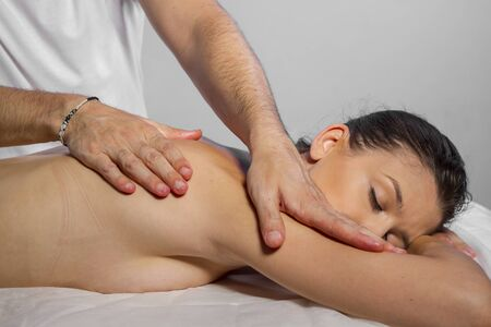 masseur: Wellness. Masseur doing massage on woman body in the spa salon. Beauty treatment concept. Stock Photo