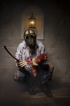 ghoulish: Man chained with blood and knife, has a severed leg blood