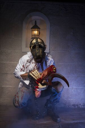 bloodied: halloween costume, Man chained with blood and knife, has a severed leg blood Stock Photo