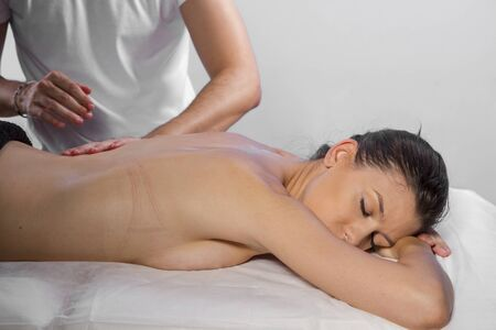 masseur: Professional masseur doing massage on woman body in the spa salon. Beauty treatment concept.