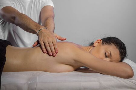 Therapy. Masseur doing massage on woman body in the spa salon. Beauty treatment concept.