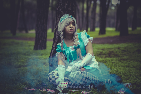 colore: costume, alice in wonderland, girl in a forest with smoke colore and playing cards