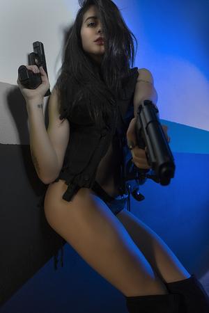 ガレージ、アクションのシーンで銃やピストルを黒革に身を包んだブルネットの少女
