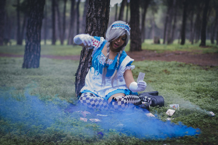 colore: imagination, alice in wonderland, girl in a forest with smoke colore and playing cards