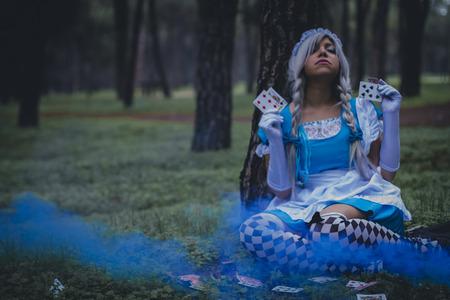 niños rubios: Alicia en el país de las maravillas, chica en un bosque con colore humo y jugando a las cartas