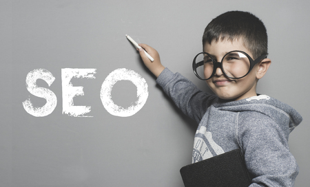 Search engine optmization, boy with glasses and funny gesture writing on the blackboard the text SEO