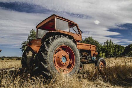 deere: farming, old agricultural tractor abandoned in a farm field Stock Photo