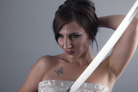 beautiful brunette girl with a Japanese sword in aggressive attitude photo
