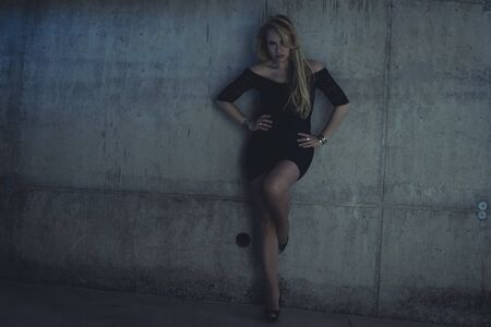 skintight: Female, blonde dressed in skintight black costume on a gray cement wall Stock Photo