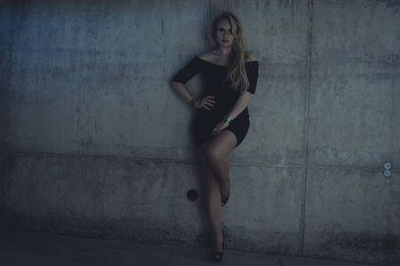 skintight: blonde dressed in skintight black costume on a gray cement wall Stock Photo
