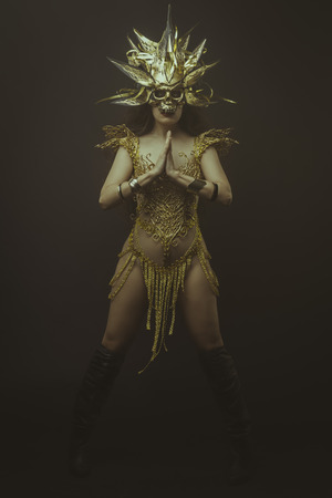 gold lace: golden mask, brunette goddess dressed in gold lace dress. concept deity and faith Stock Photo