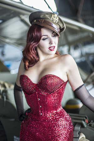 Sexy and beautiful redhead pin up style wearing uniform wii with vintage aircraft war