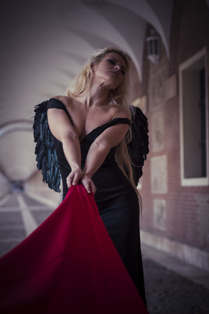 Love, an angel in the city, beautiful blonde with long hair dressed in black and with black wings