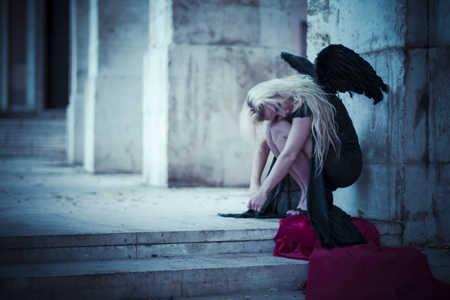 an angel in the city, beautiful blonde with long hair dressed in black and with black wings
