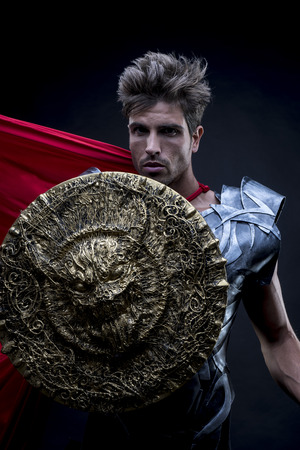enactment: Epic, centurion or Roman warrior with iron armor, military helmet with horsehair and sword Stock Photo