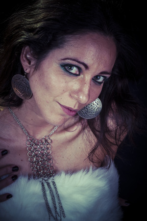 silver jewelry, sensual woman brunette with gold and silver in the neck, dressed in white fur