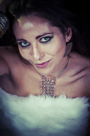 Diamond, silver jewelry, sensual woman brunette with gold and silver in the neck, dressed in white fur