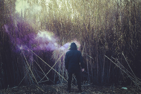 Loneliness and depression, solitary man with colored smoke
