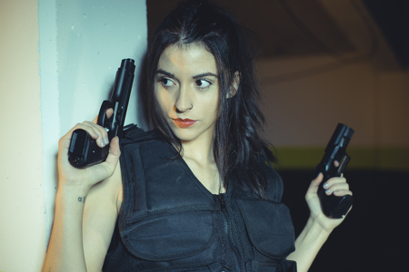 Model brunette girl with gun in a garage in attitude shoot, dressed in bulletproof vest Stock Photo