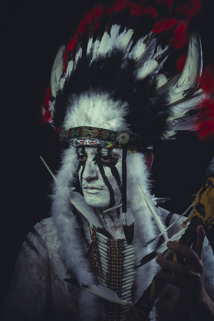 American Indian chief with feather headdress and traditional war ax