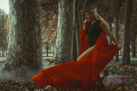 Fashion, concept autumn blond woman with huge metal helmet and red cape, goddess of forests, fantasy