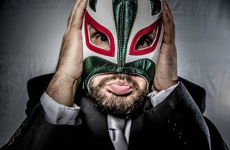 yell: Angry businessman with mask of Mexican fighter, dressed in suit and tie