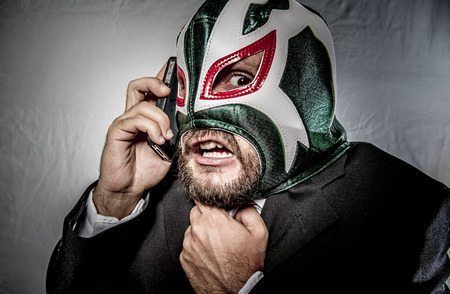 Scream, Angry businessman with mask of Mexican fighter, dressed in suit and tie