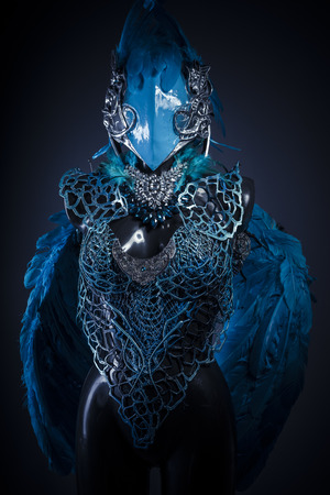 Cosplay, Handmade styling of a bird or mythological figure with blue wings and pieces of metal and precious stones Stock Photo