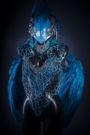 hair feathers: Handmade styling of a bird or mythological figure with blue wings and pieces of metal and precious stones Stock Photo