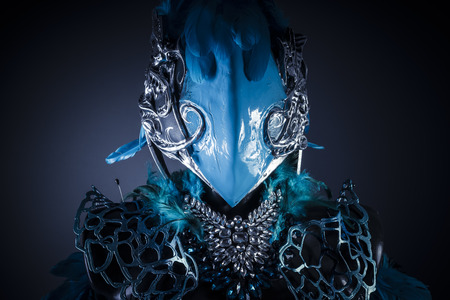 Handmade styling of a bird or mythological figure with blue wings and pieces of metal and precious stones Stock Photo