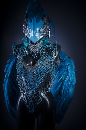 winds: Cosplay, Handmade styling of a bird or mythological figure with blue wings and pieces of metal and precious stones Stock Photo