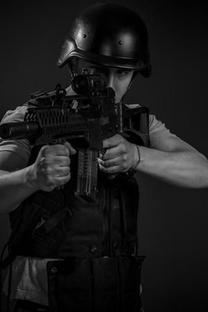 Warfare, paintball sport player wearing protective helmet aiming pistol ,black armor and machine gun