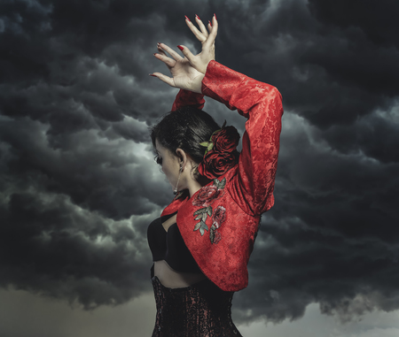 Spanish flamenco dancer with bun in hair and red coat with storm background in the sky
