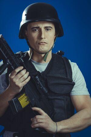 gunfire: Air-soft, paintball sport player wearing protective helmet aiming pistol ,black armor and machine gun Stock Photo