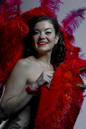 Burlesque girl with red bird feathers and pheasant with pretty smile