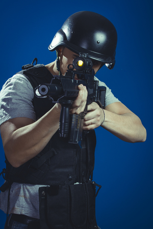 Safety, paintball sport player wearing protective helmet aiming pistol ,black armor and machine gun Stock Photo