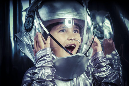 Boy playing to be an astronaut with space helmet and metal suit photo