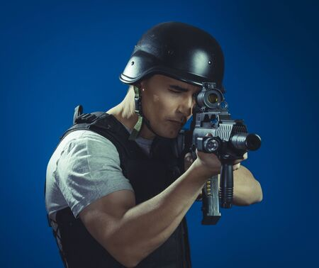 gunfire: Targeting, paintball sport player wearing protective helmet aiming pistol ,black armor and machine gun Stock Photo