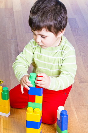 Funny little boy playing with plastic colorful blocks, studio shot photo
