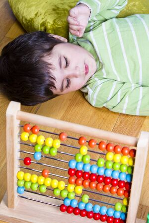 Funny little boy playing with abacus, studio shot photo