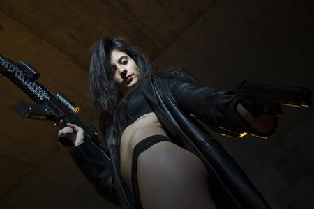 Firearm, Army brunette girl with gun in a garage in attitude shoot, dressed in bulletproof vest Stock Photo