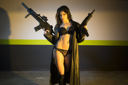 machinegun: Armed and dangerous brunette girl with a gun and a machine-gun in a garage at night Stock Photo