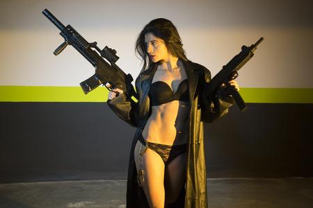 militaire sexy: fille brune armée et dangereuse avec un fusil et une mitrailleuse dans un garage la nuit
