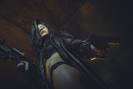 Agent, Army brunette girl with gun in a garage in attitude shoot, dressed in bulletproof vest