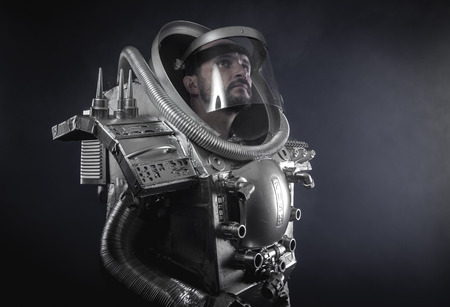 Gravity, Space man, astronaut dressed in silver or metalized space suit. Armed with a laser gun and surrounded by smoke Stock Photo