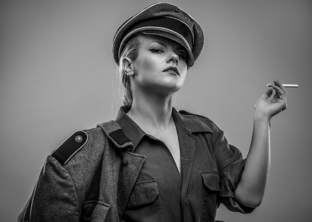 Smoking, German officer of the Second World War. Woman with power, dominant and severe Stock Photo